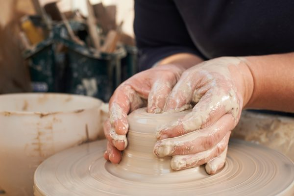 two hands making japanese pottery